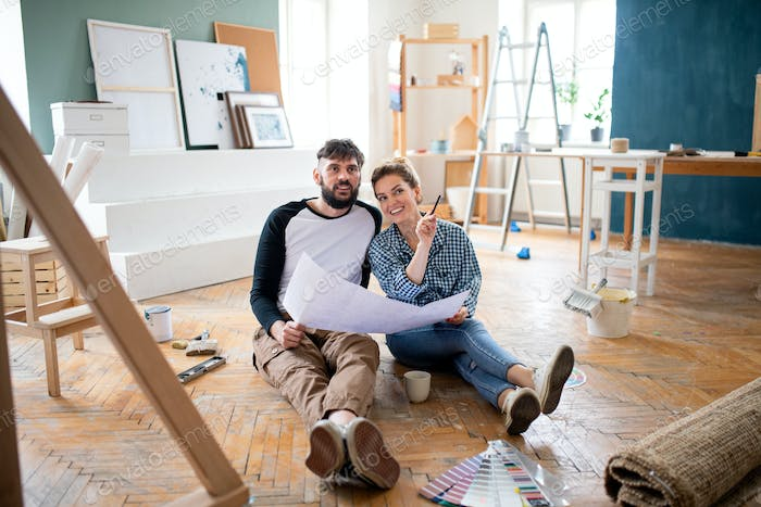 Mid adults couple planning indoors at home, relocation and diy concept