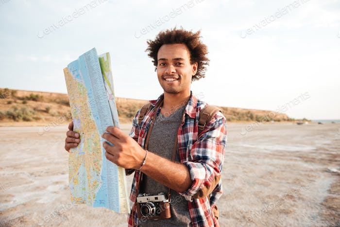 Happy man tourist with backpack standing and holding map outdoors