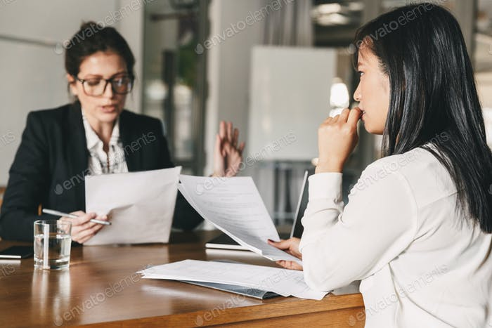 Image of nervous asian woman looking and talking to businesswoma