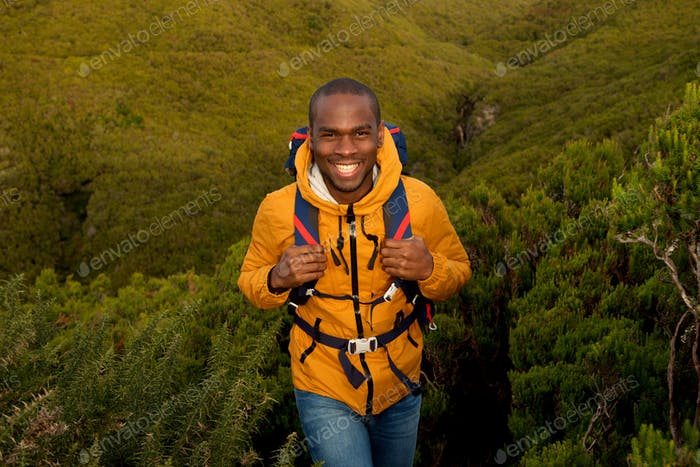happy young black man hiking in nature with backpack