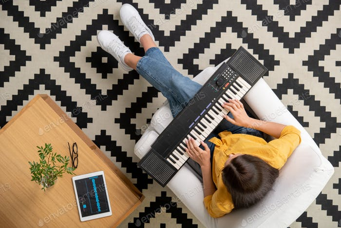 Overview of young brunette female touching keys of synthesizer keyboard