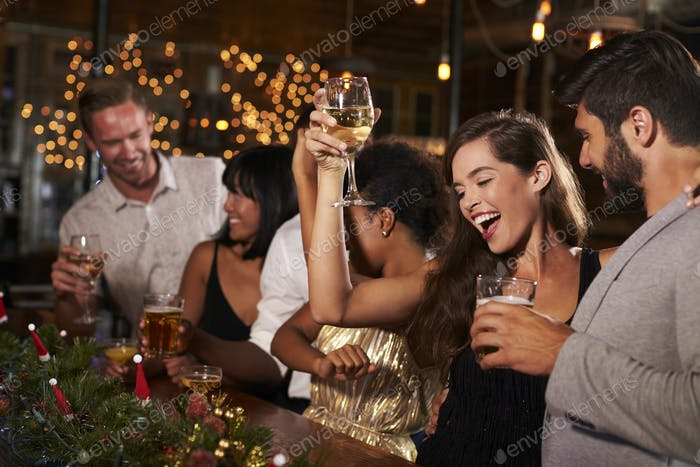 Woman raising a glass at a Christmas party in a bar