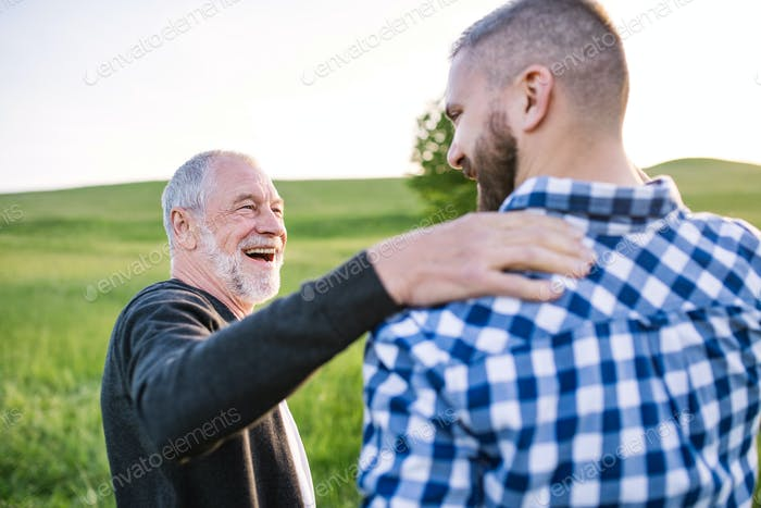 An adult hipster son with senior father on a walk in nature at sunset, talking.