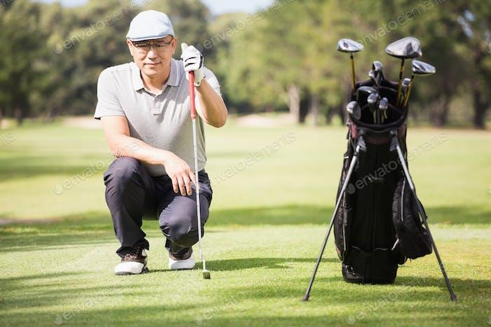 Golfer crouching and posing