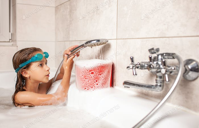 Funny little girl bathes in a bathtub and pours water into the bucket