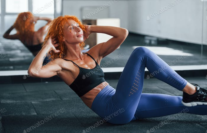 Doing abs. Sporty redhead girl have fitness day in gym at daytime. Muscular body type