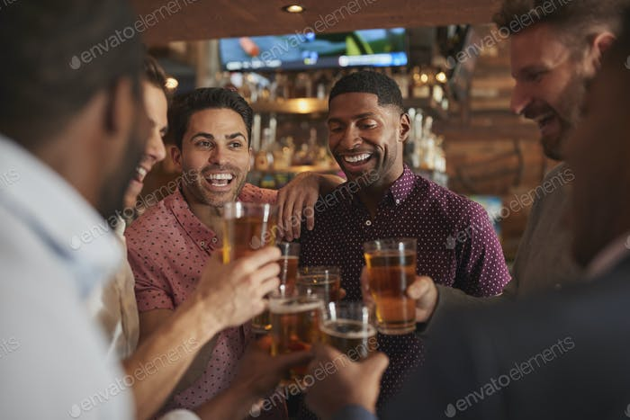 Group Of Male Friends On Night Out Drinking Beer In Bar Together