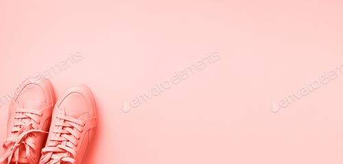 Woman fashion pink shoes on trendy coral color background with copy space. Top view. Flat lay