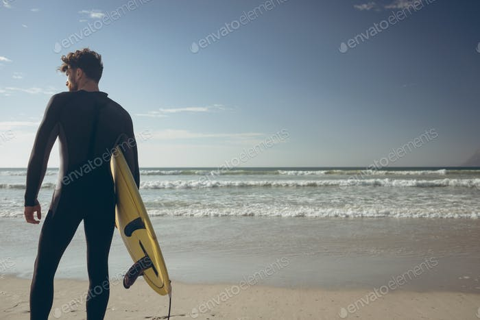 Young male surfer with a surfboard standing on a beach on sunny day