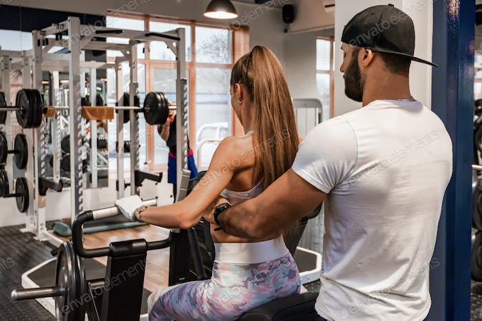 Back view personal trainer coaching female bodybuilder on machine in modern gym