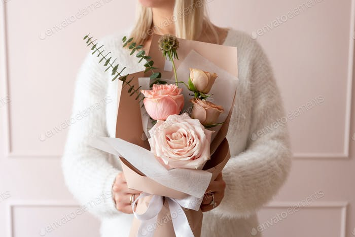 Frau hält einen Blumenstrauß Rosen
