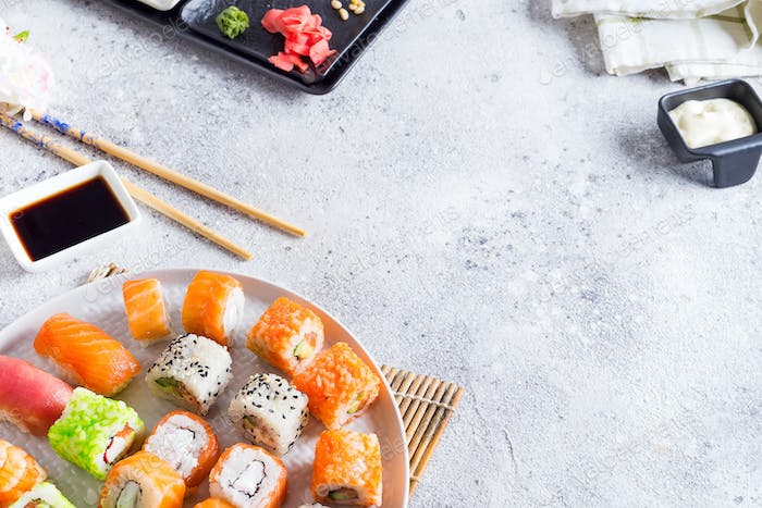 Various Fresh and delicious sushi set on white slate with wooden sticks, sauce on light stone
