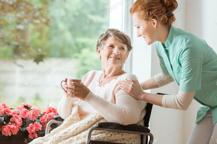 Ein professioneller Hausmeister in Uniform hilft einer geriatrischen weiblichen p