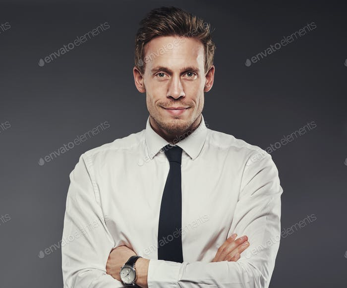 Smiling young businessman standing confidently against a grey background