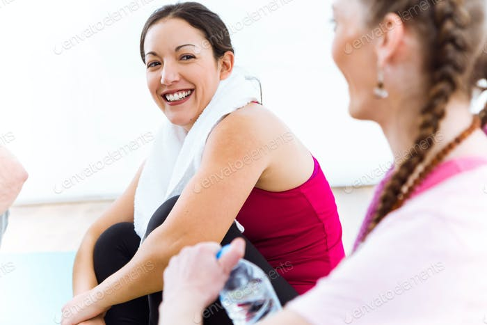 Couple relaxing on yoga mat and talking after workout session.