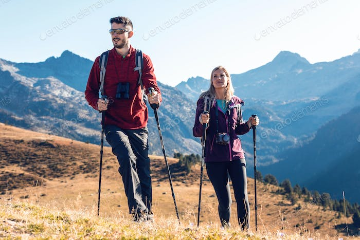 Two travel hikers with backpack walking while looking the landscape in the mountain.