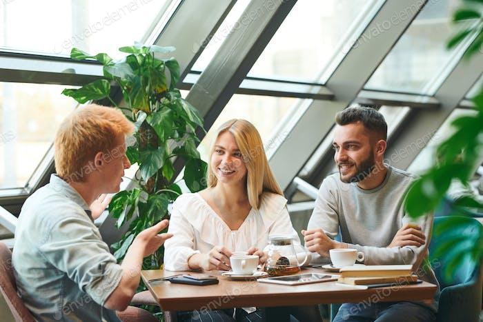 Gruppe von jungen zeitgenössischen Studenten versammelt nach Tisch im Café nach dem Unterricht