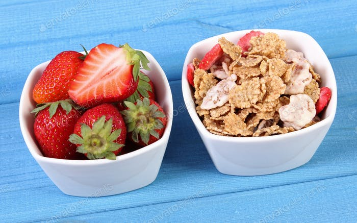 Fresh strawberries, wheat and rye flakes in bowl on boards, healthy lifestyle and nutrition