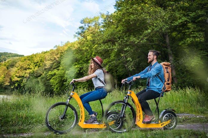 Junge Touristenpaare Reisende mit Elektrorollern in der Natur