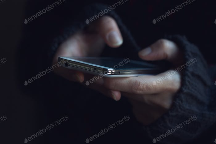 Close up of woman in dark sweater hands holding a phone