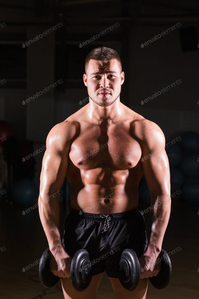 Muscular bodybuilder guy doing exercises with dumbbells.
