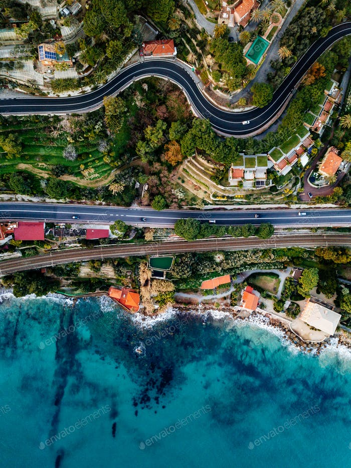 Aerial view of road, highway and railway going along ocean or sea. Drone photography in rural Italy