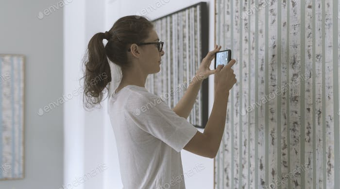 Woman standing in the art gallery and taking pictures