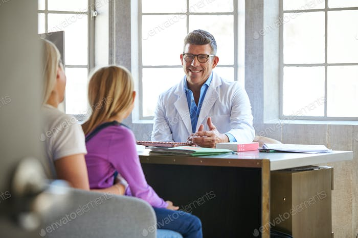 Mother And Daughter Meeting With Hospital Consultant In Office