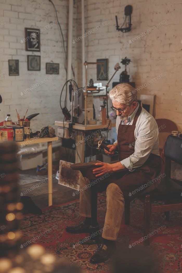 Elder cobbler in the workshop