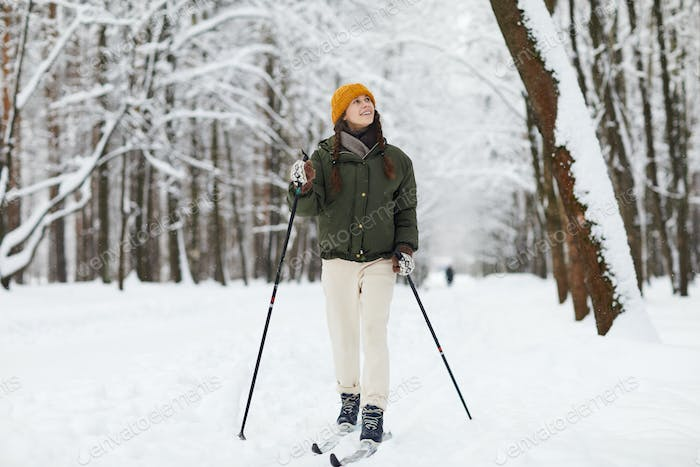 Cheerful Woman Skiing in Forest