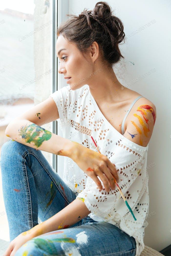 Nachdenkliche junge Frau schmutzig mit Farben Blick auf das Fenster
