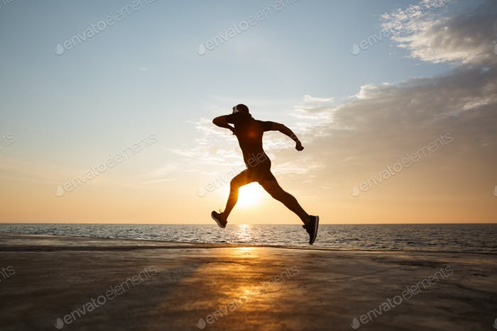 Silhouette of athletic guy 30s in shorts and t-shirt training an
