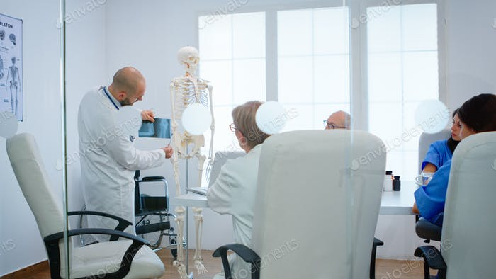 Physician learning colleagues body bone functionson using x-ray and human skeleton