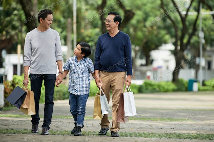 Boy walking with father and grandfather after shopping