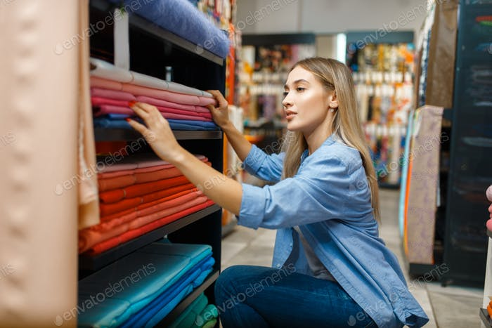 Saleswoman measures fabric in textile store