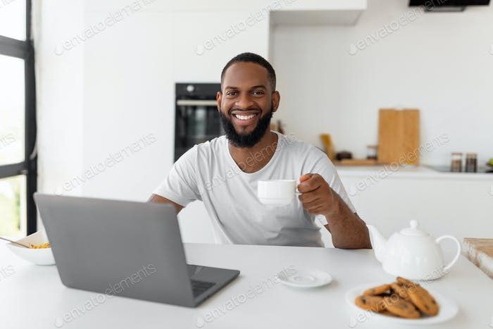 African American man using laptop drinking coffee looking at camera