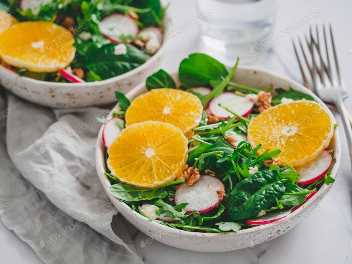 Salad bowl with oranges, spinach, arugula, radish