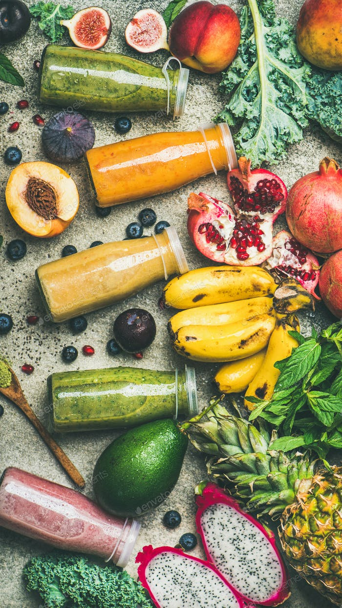 Colorful smoothies in bottles with fresh tropical fruit, top view