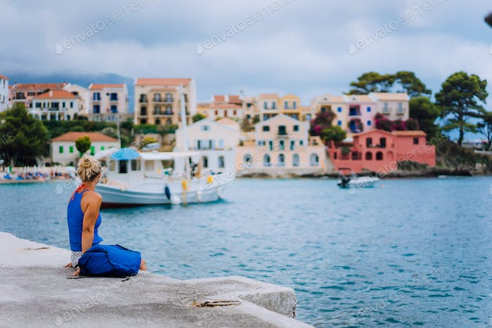 Woman tourist sitting on the pier and looking to the picturesque bay. Assos village with beautiful