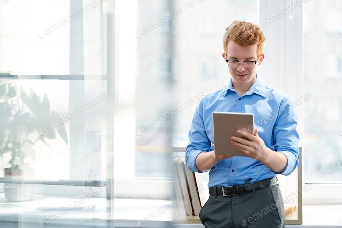 Молодой человек в формальной одежде прокрутки в планшете