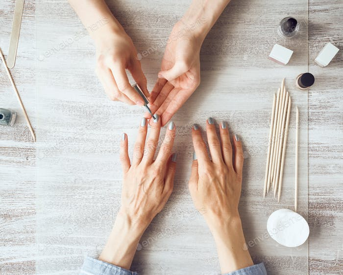 Mother and daughter do manicure, paint nails with varnish. Home self-care during quarantine