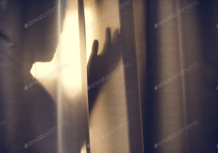 Human shadow behind a curtain