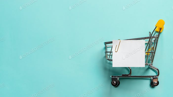 Shopping cart and white paper note list on blue