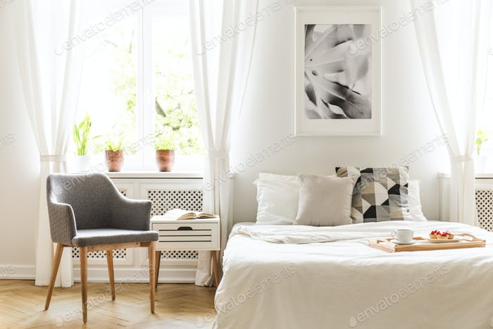 Grau Sessel neben Bett mit Holztablett in hellen Schlafzimmer int