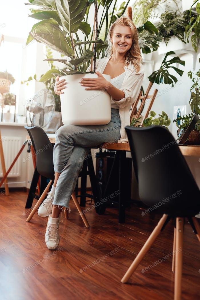 Glad female freelancer wearing casual clothing with houseplant