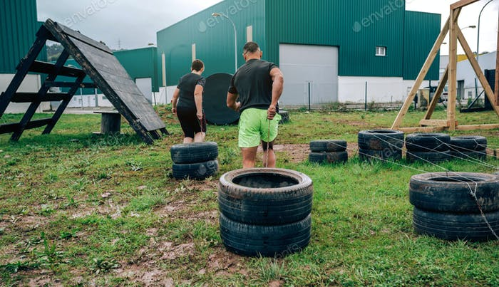 Participants in an obstacle course dragging wheels