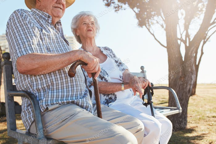 Senior couple sitting on a bench with walking stick