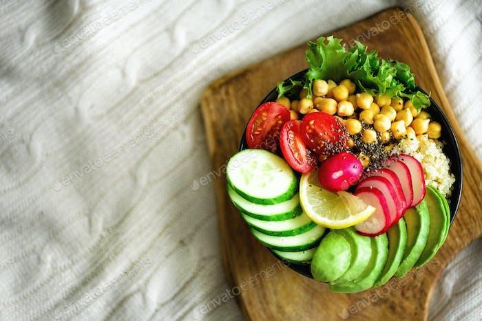 Buddha bowl with avocado, quinoa, cucumber, radish, salad, lemon, cherry tomatoes, chickpea, chia