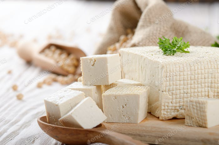 Sojabohnenquark Tofu auf Schneidebrett und im Hanfsack auf weiß