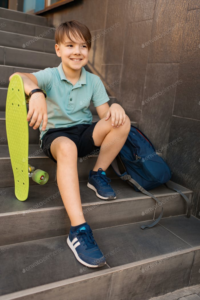 Boy sitting on the stairs with a backpack and penny